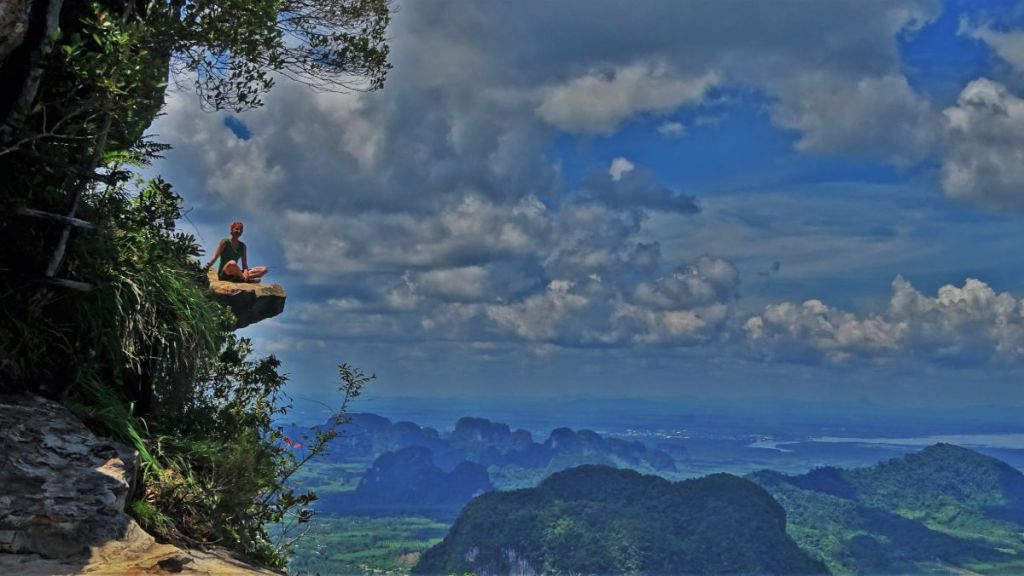 Weronika sitting on t 'hanging in the air' rock with karst formations, blue sky with white clouds in the background