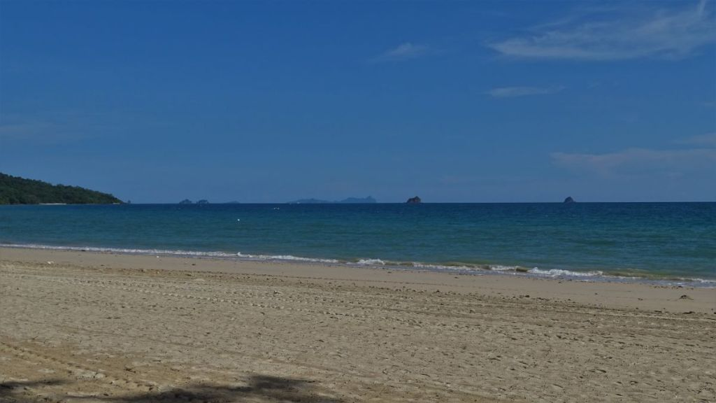 Empty Klong Muang beach with white sand and few far away karst formations in the blue sea in Krabi