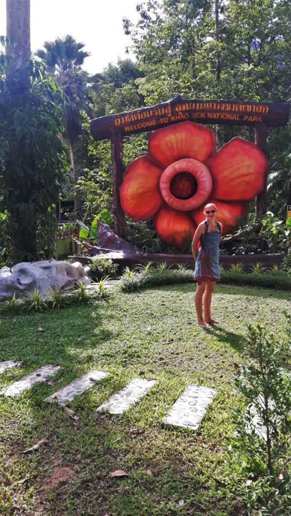 Weronika standing in front of 'welcome to Khao Sok National Park' signboard with huge wooden red flower