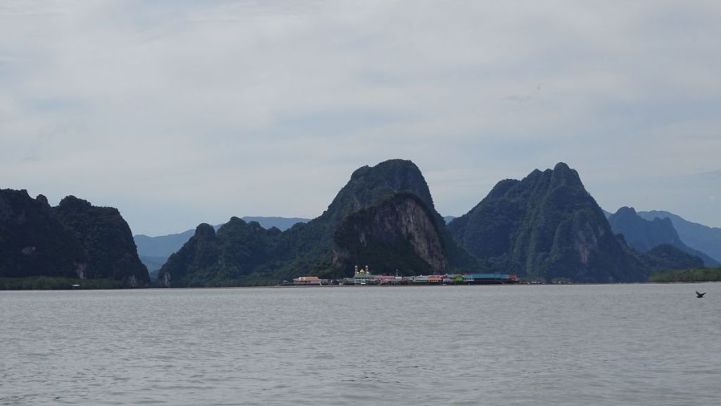 The floating village from the boat and karst formations in the background