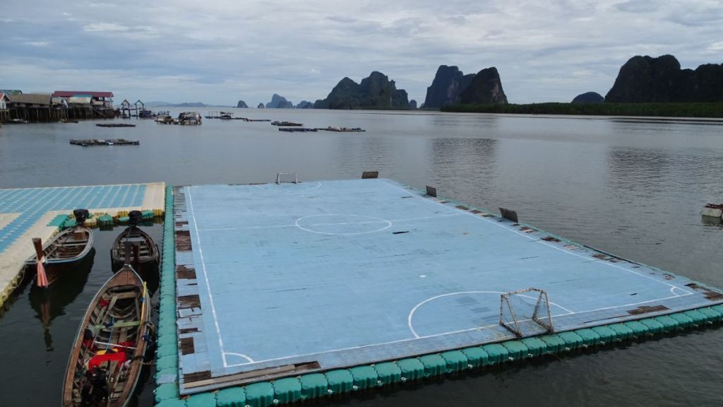 A floating small football pitch with karst formations in the background and few boats by the side