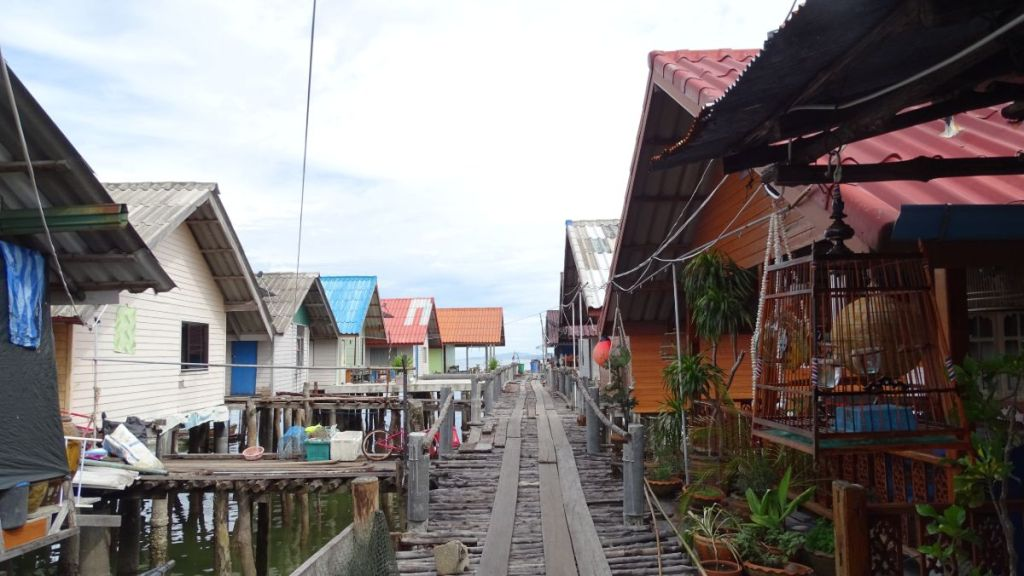 A wooden path on stilts in the floating village with the houses on both side