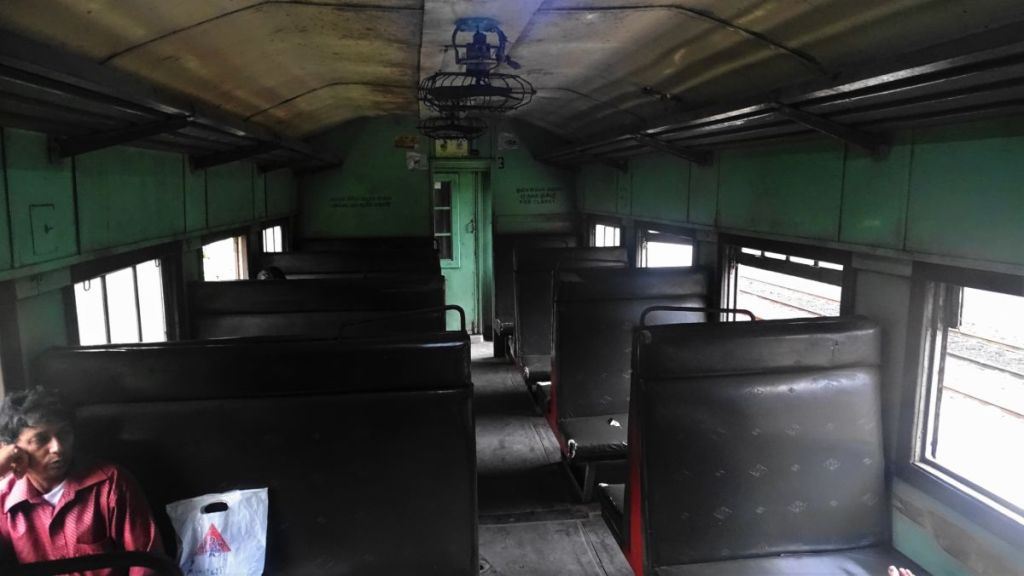 Just one man sits in an empty car of the 3rd class of Sri Lankan train