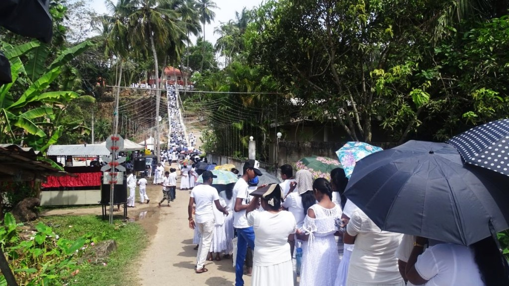 A few hundred meters long queue of white-dressed devotees wait to enter a Buddhist temple in Talpe, Sri Lanka