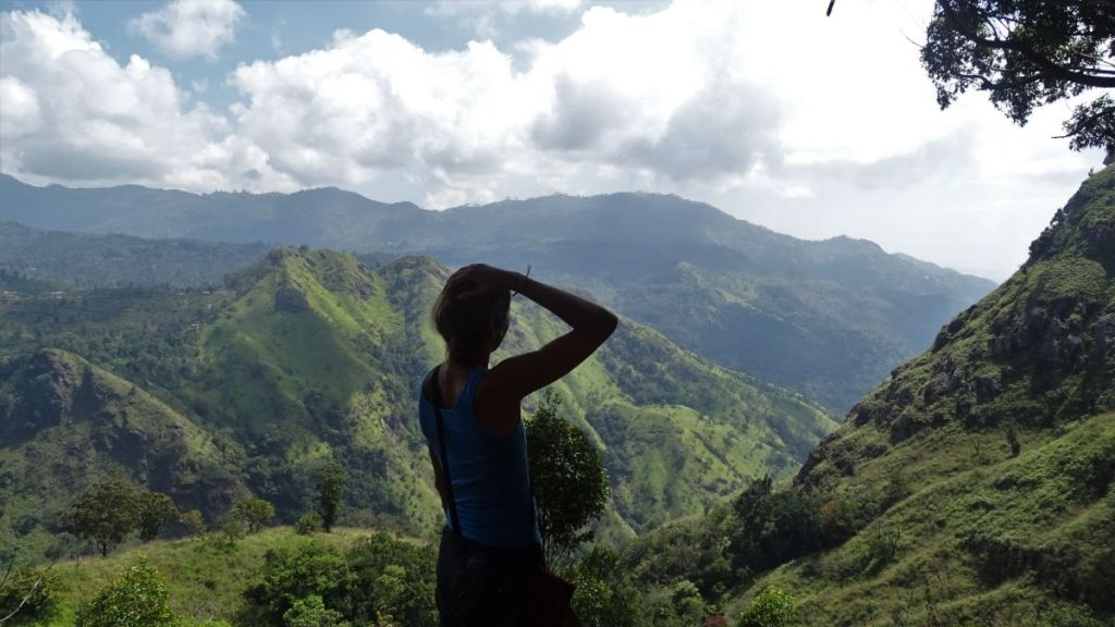 Weronika looks at the green mountains and a deep valley below on the way to Ella Rock in Sri Lanka