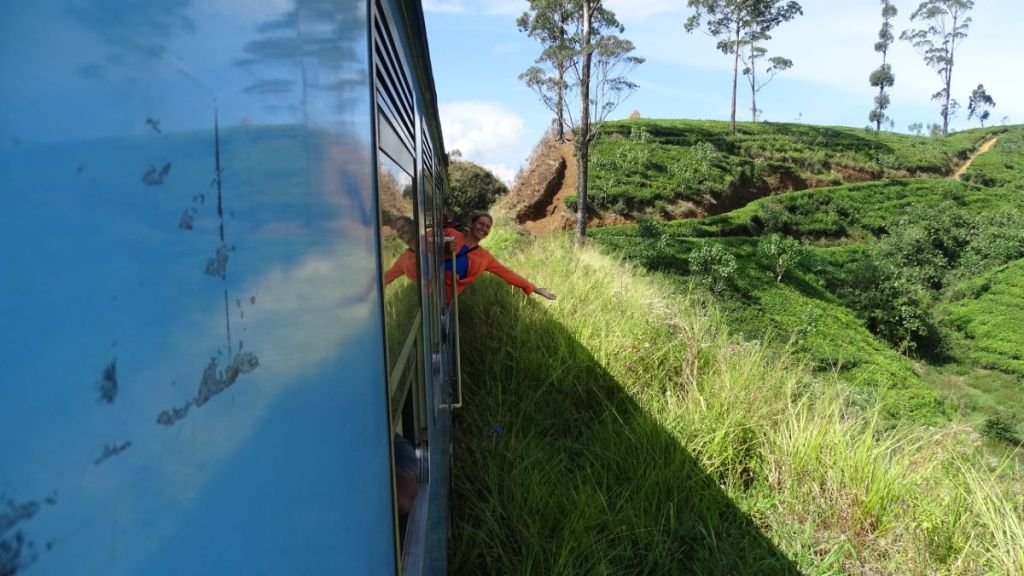 Weronika sticks her upper body out of the train passing through the tea plantations in Sri Lanka