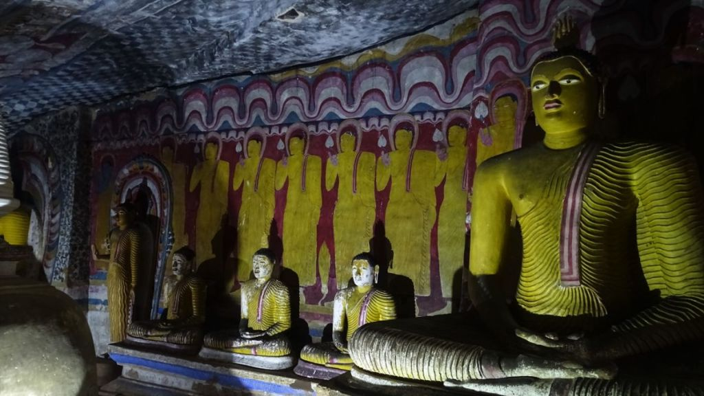 Dark interior of Dambulla cave temple: statues of seated Buddha and paitings of his devotees in the background
