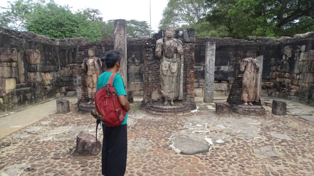 Sayak looks at the stone standing Buddha statues among the ruins of Polonnaruwa in Sri Lanka