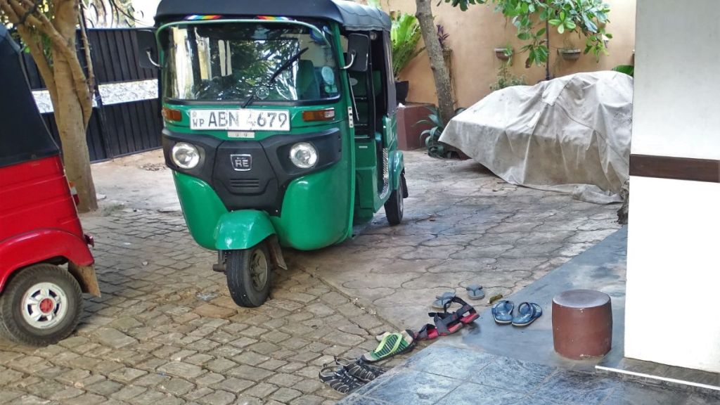 A green tuk-tuk parked on the courtyard.