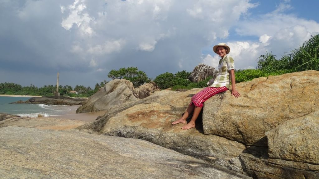 Weronika sits on large boulders on the coast in Balapitiya, Sri Lanka, wearing a shirt and knee-length sarong.