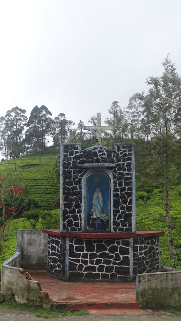 A rock road shrine with a figure of Mother Mary set among Lipton tea plantation in Sri Lanka