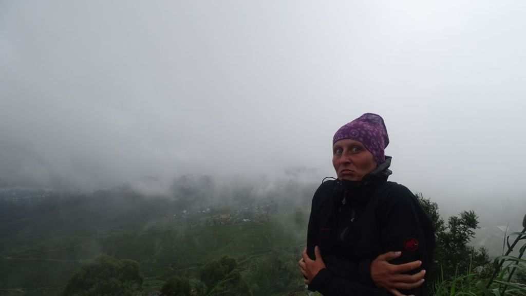 Weronika expresses her displeasure from cold, foggy weather in Haputale, Sri Lanka. Green tea hills in the background.