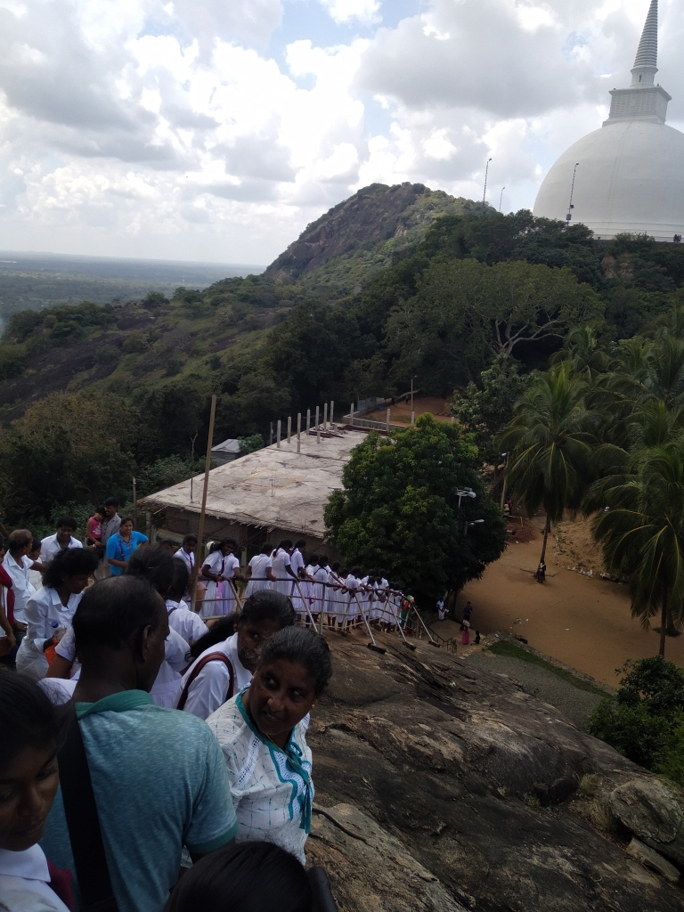 A long queue of white-dressed Sri Lankan ladies wait to climb Mihintale rock. A large white stupa on the background