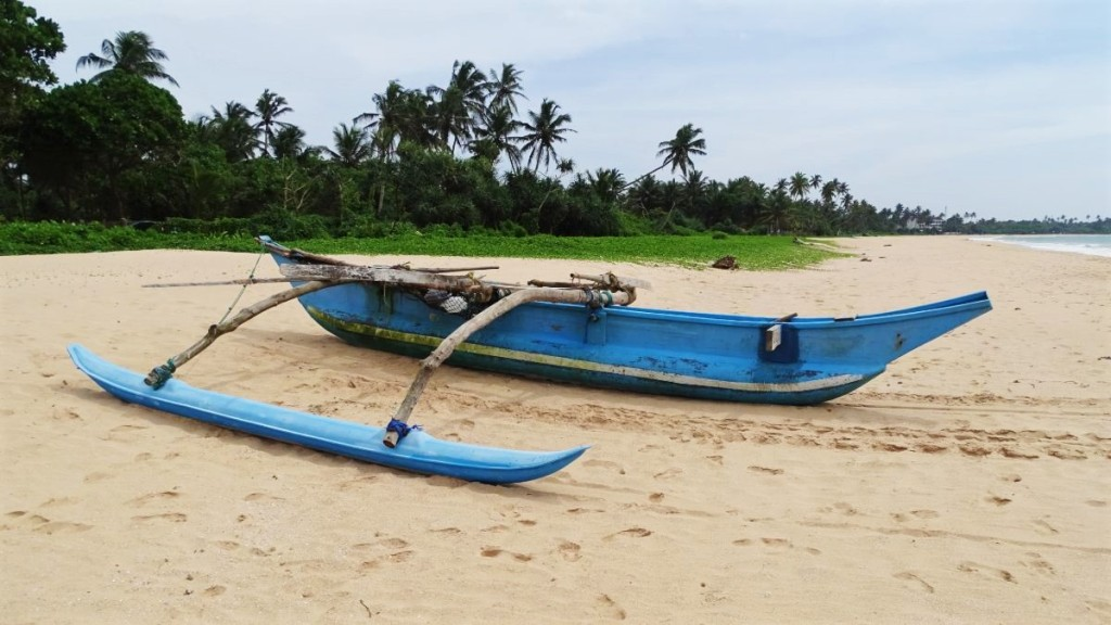 A traditional Sri Lankan wooden fishing boat lies on a long, empty, sandy beach in Balapitiya