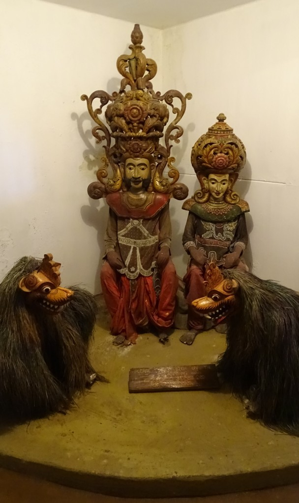 Two huge, ornamental wooden masks of a man and a woman on manequins and two hairy masks of lions at a display at Mask Museum in Ambalangoda
