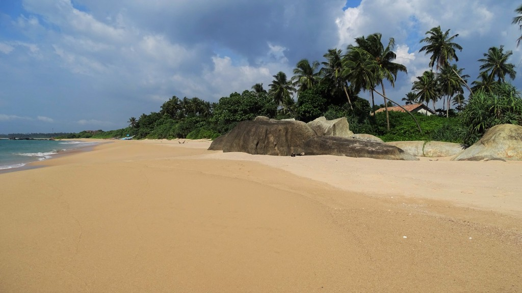 A long, white-sand beach with one huge boulder and a line of greenery and coconut palms in Balapitiya, Sri Lanka