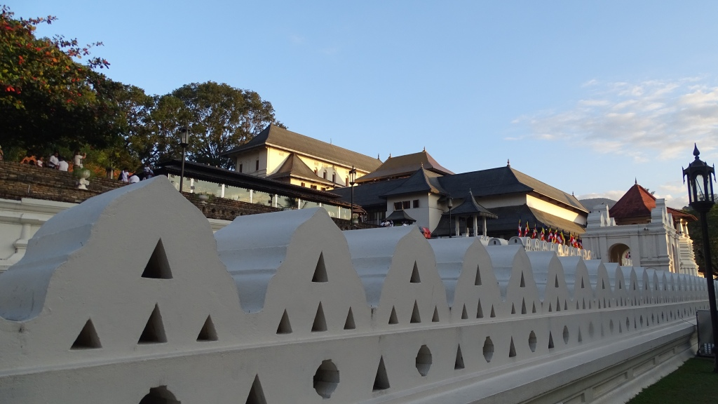 A white stone fence surrounding a few storey-tall Temple of the Sacred Tooth in Kandy, Sri Lanka