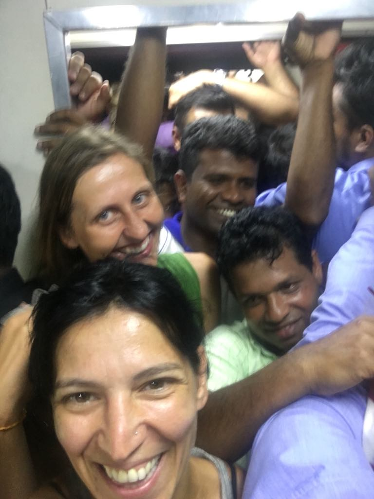 The  smiling author and her friend stand in an extremely crowded train in Sri Lanka surrounded with local men.