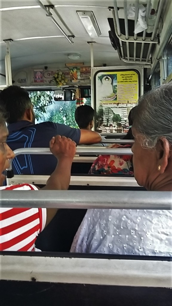Locals sit on the bus in Sri lanka, decorated with Buddha images.