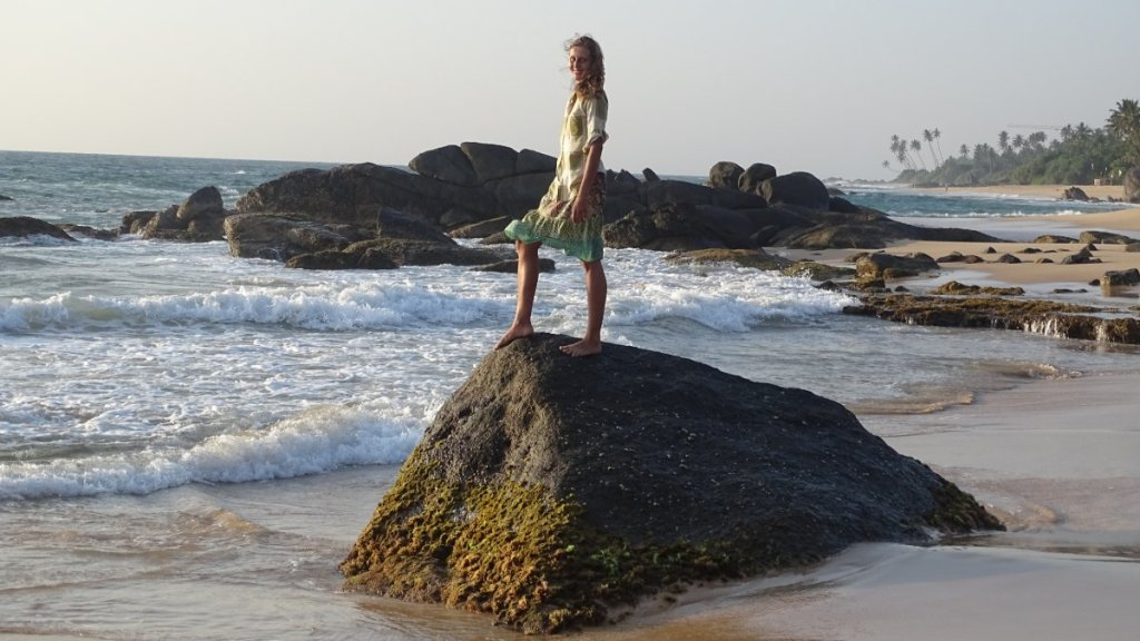 The author standing on a boulder on the beach in Ambalangoda, some rocky outcrops, sand and palms behind her