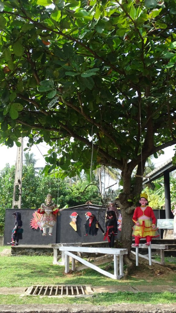 Colourful puppets of men and demons hanging from a tree in Balapitiya, Sri Lanka