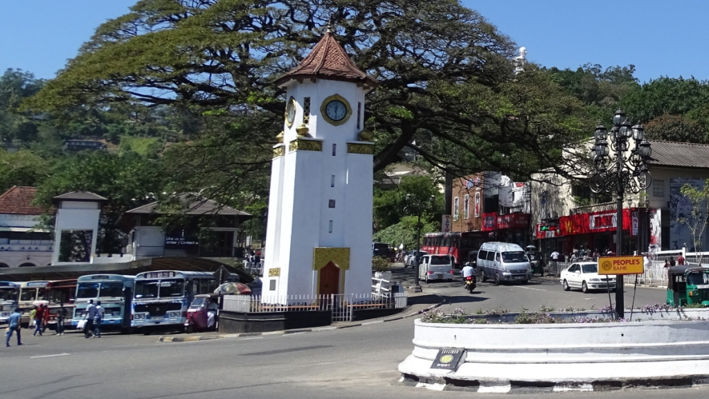 A clocktwoer and roundabout next to a bus station in Kandy, Sri Lanka