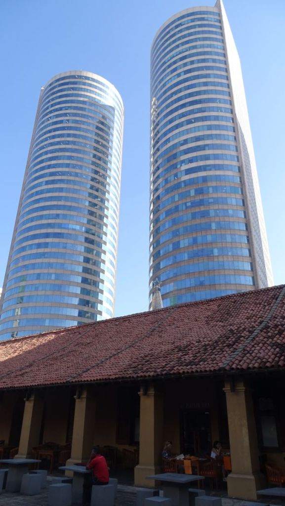 High-rise, modern towers rising from behind the old colonial building converted to a restaurant in Colombo, Sri Lanka
