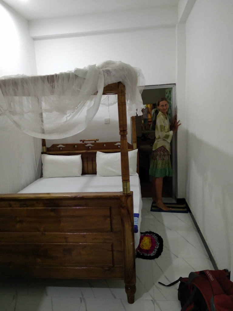 The author standing in a small but very clean and new room, next to a canopy bed in Mirissa, Sri Lanka