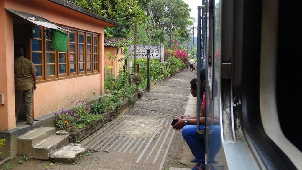 Two Sri Lankan men sit in the doors of a train standing at a tiny station in Upcountry