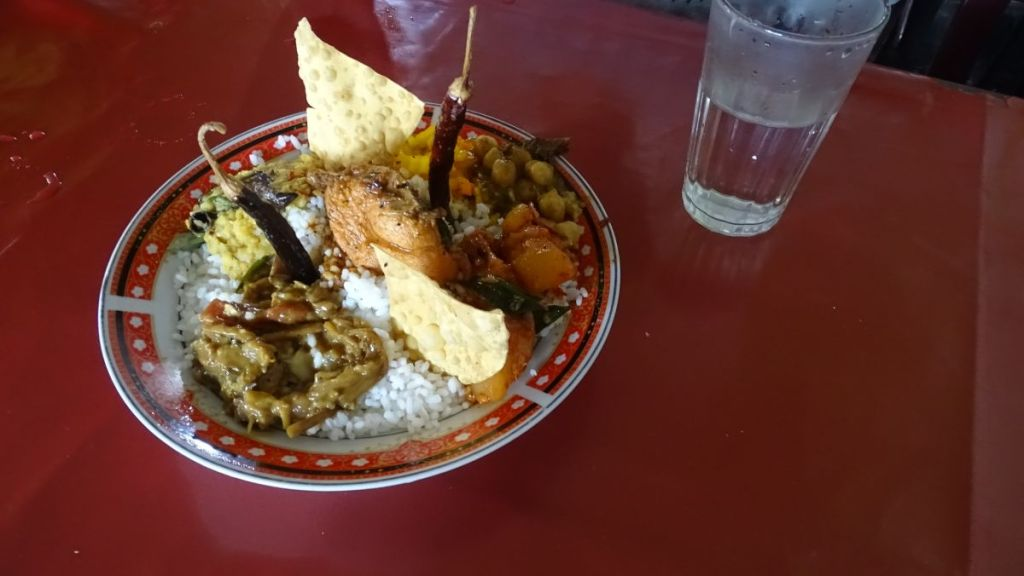A plate of rice and a selection of curiries with dried chillies stuck on top lie on a plastic table in a roadside Sri Lankan eatery