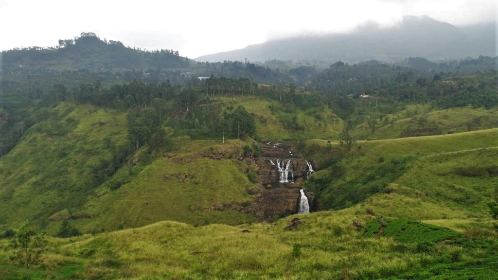 Large, three-tier, wide St Clair falls set among rollling green hills and a rising mist near Nuwara Elliya in Sri Lanka