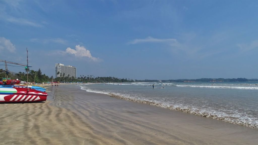 Shallow water at the Weligama beach enjoyed by beginner surfers. A large high rise hotel in the background.