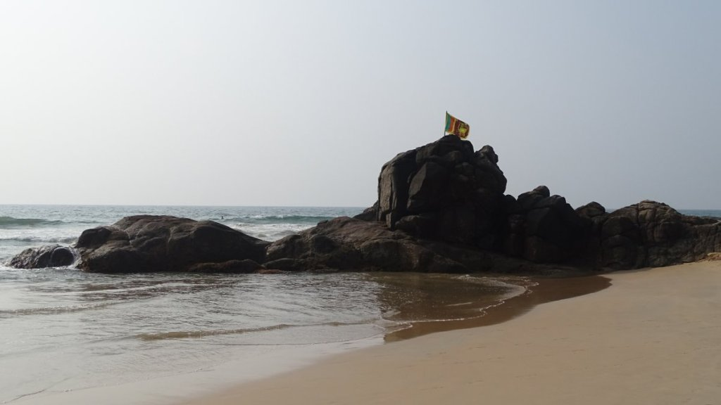 A rocky outcrop on a sandy beach in Bentota, decorated with a Sri Lankan flag