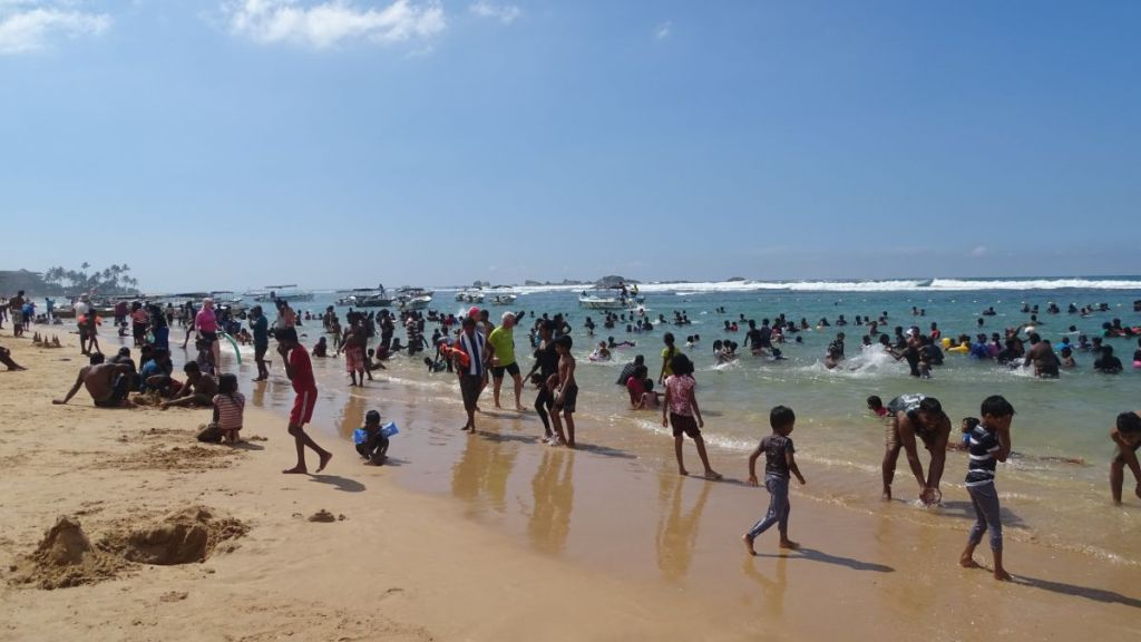 A dense crowd of fully-dressed Sri Lankans on the narrow strip of the beach in Hikkaduwa
