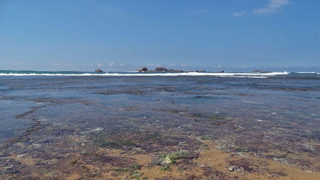 Ankle-deep water covers flat-stone seabank reaching some 50 meteres far into the sea in Hikkaduwa, Sri Lanka