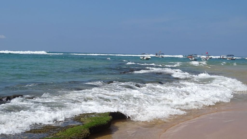 Rocks coming out of the water on otherwise sandy beach in Hikkaduwa, small boats bobbig on the waves on the horizon