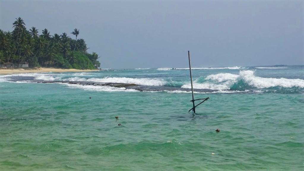 Waves break at the rocks creating a natural, turqoise colour pool on Kogalla beach in Sri Lanka