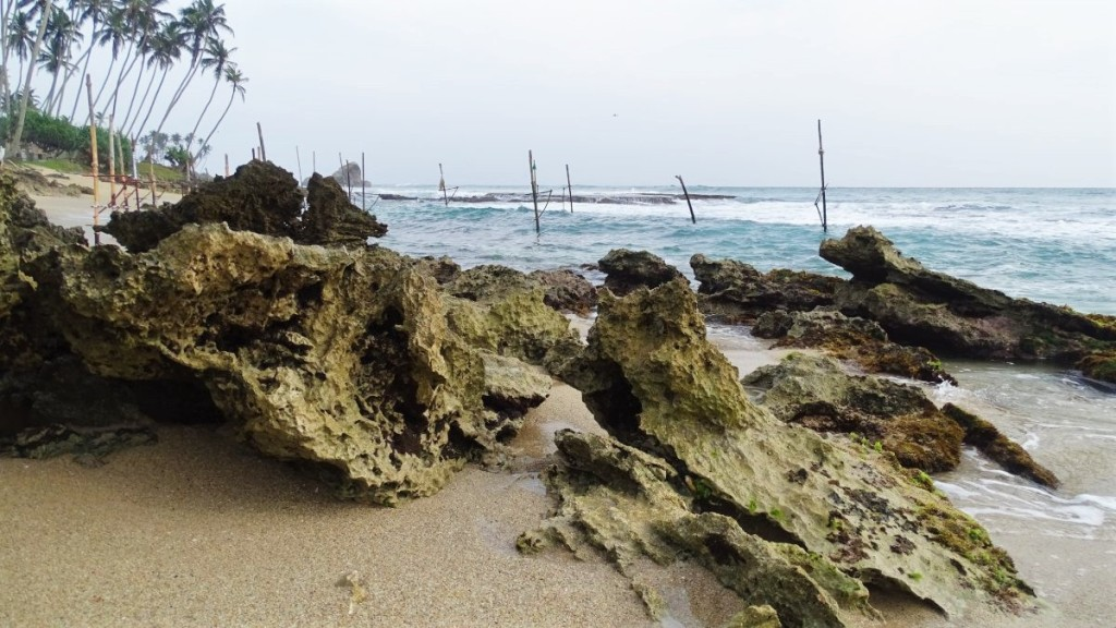 A few slits used traditionally for fishing in Sri Lanka stands in the shallow waters of Koggala beach where sand mixes with eroded rocks