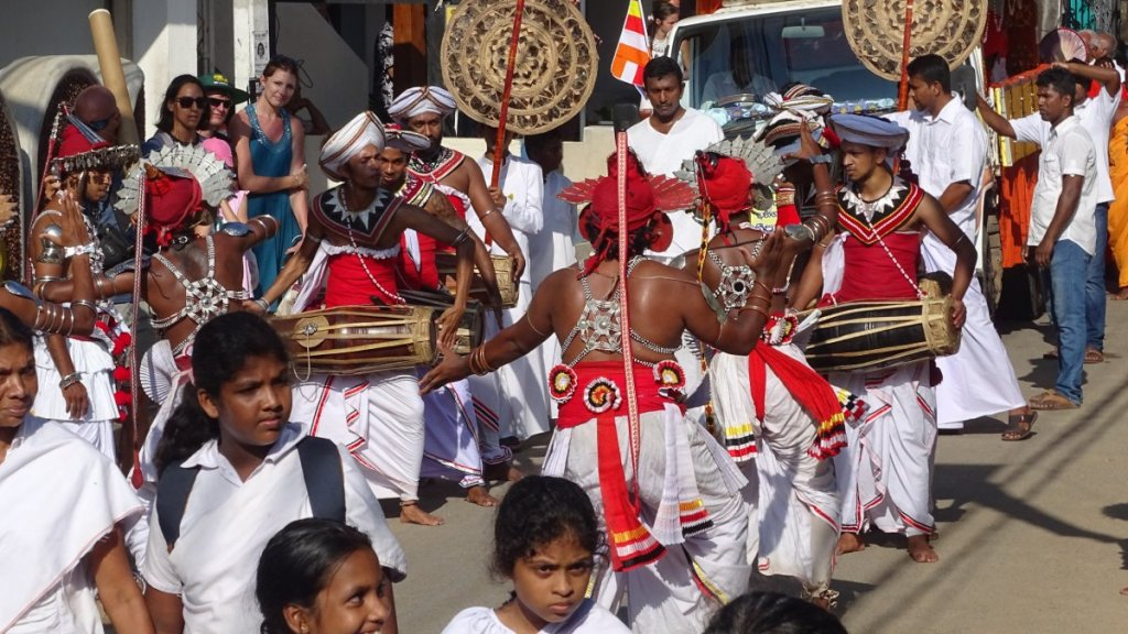 Poya procession in Unawatuna, Sri Lanka, including girls dressed in white, male dancers in white dhotis and metal headdress and ornaments on the torso and a truck with Buddhist monks