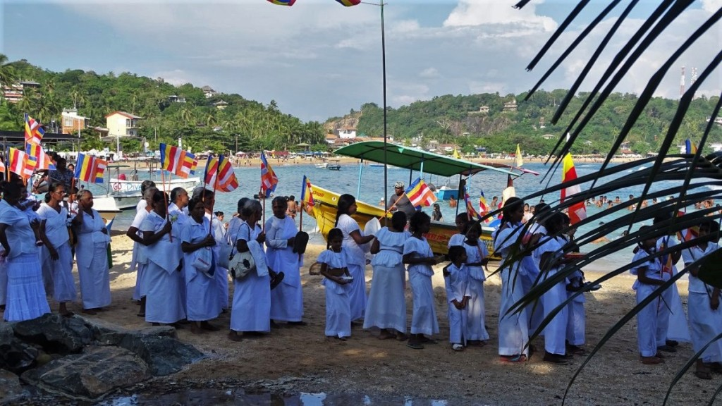 A large group of female Buddhist devotees dressed in white and carrying flags marches through the beach in Unawatuna to reach the temple during Poya festival