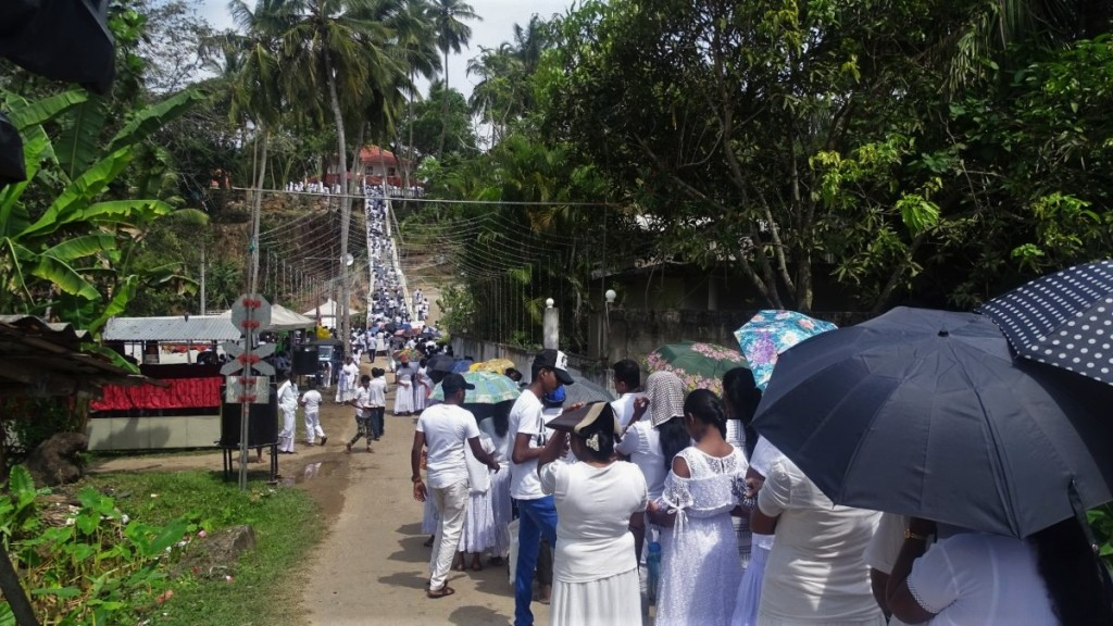 A few hundred meters long queue of white-clad Buddhist devotees stand in a queue climbing up the temple on a small hill in Talpe, Sri Lanka