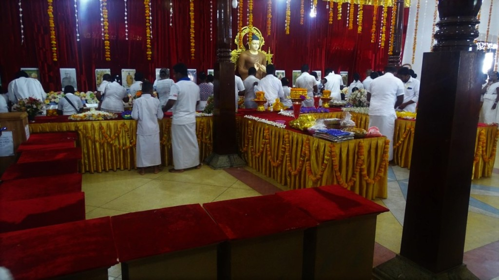 A queue of white clad Buddhists pay respect inf front of relics of Buddha and revered monks in Talpe, Sri Lanka