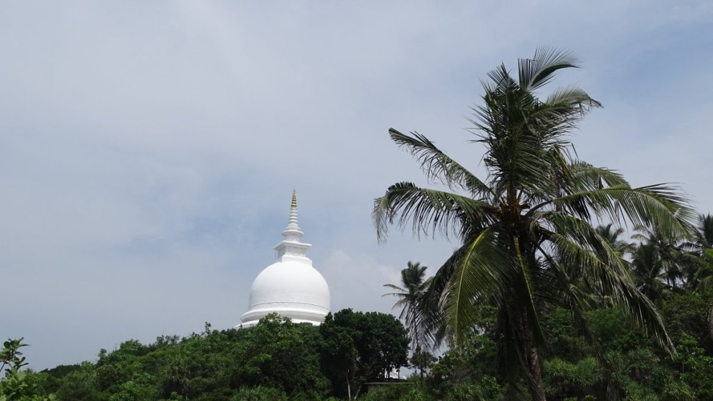 A white stupa stands among the trees on top of a hill in Unawatuna, Sri Lanka