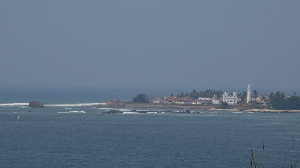 A view across the bay at Galle old town surrounded with city walls and a white lighthouse