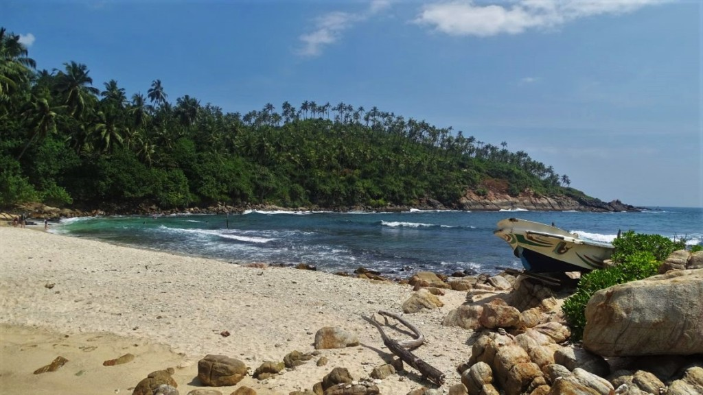 A small, sandy Secret Beach in Mirissa, closed on one side by rocky outcrop and on the other by a peninsula covered with lush greenery