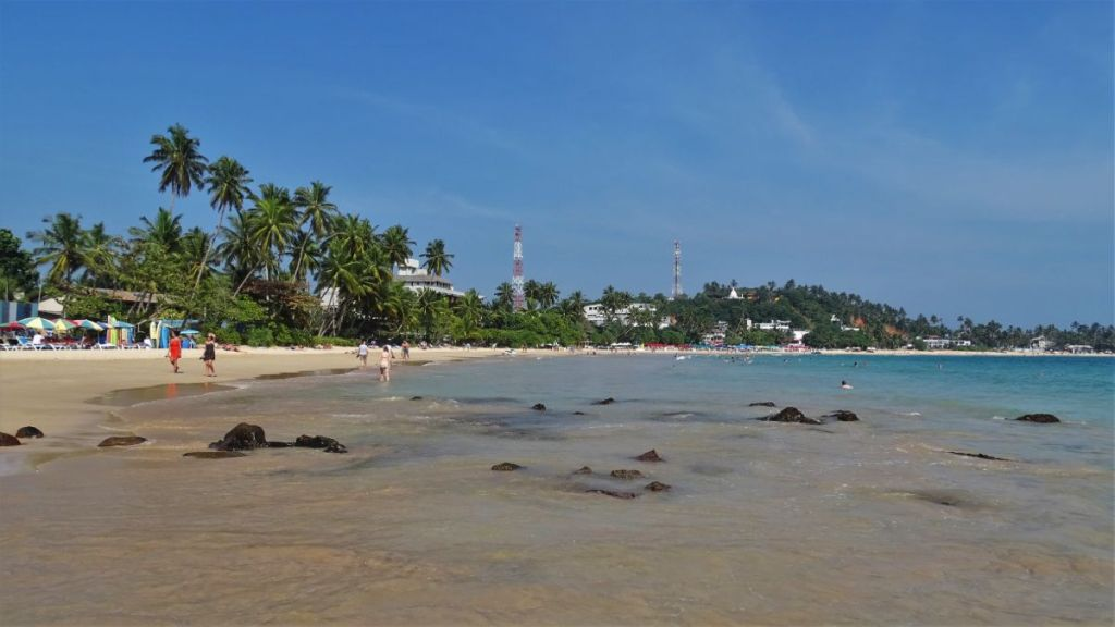 Scattered groups of people walk along the beach and stay in turquoise water along Mirissa Beach