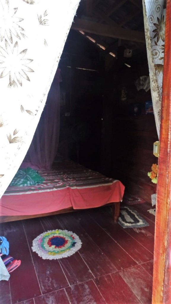 A dark interior of a small wooden hut - a budget accommodation option in Mirissa