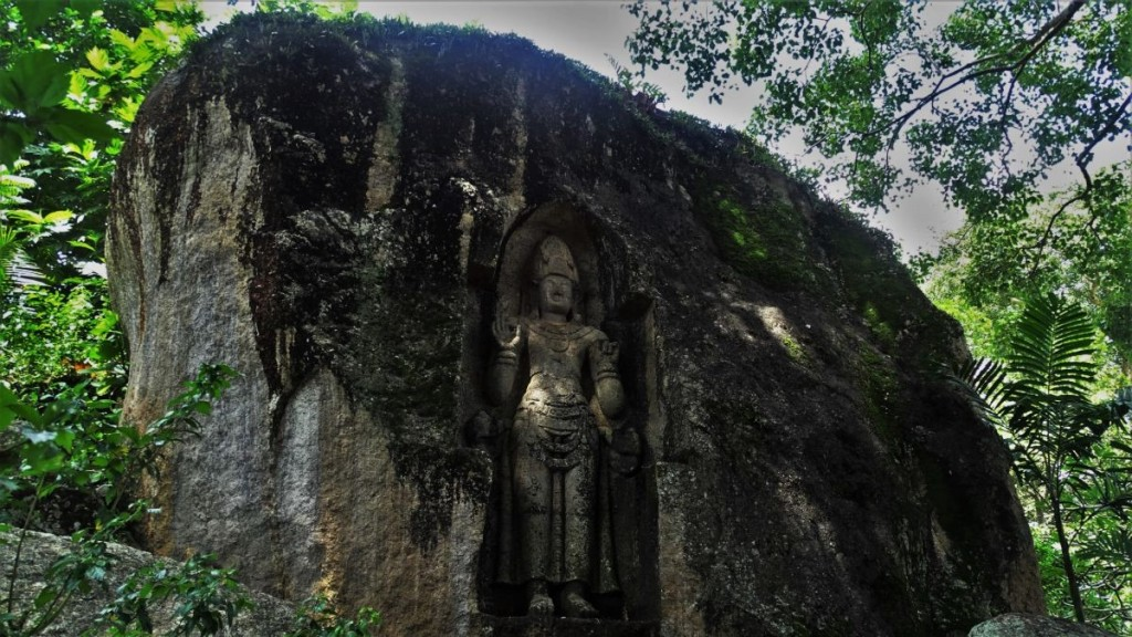 An ancient statue of a standing Buddha carved in a stone in Weligama