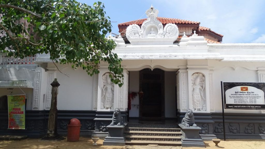 The white washed walls and sculpted entrance to a small ancient Buddhist temple in Weligama