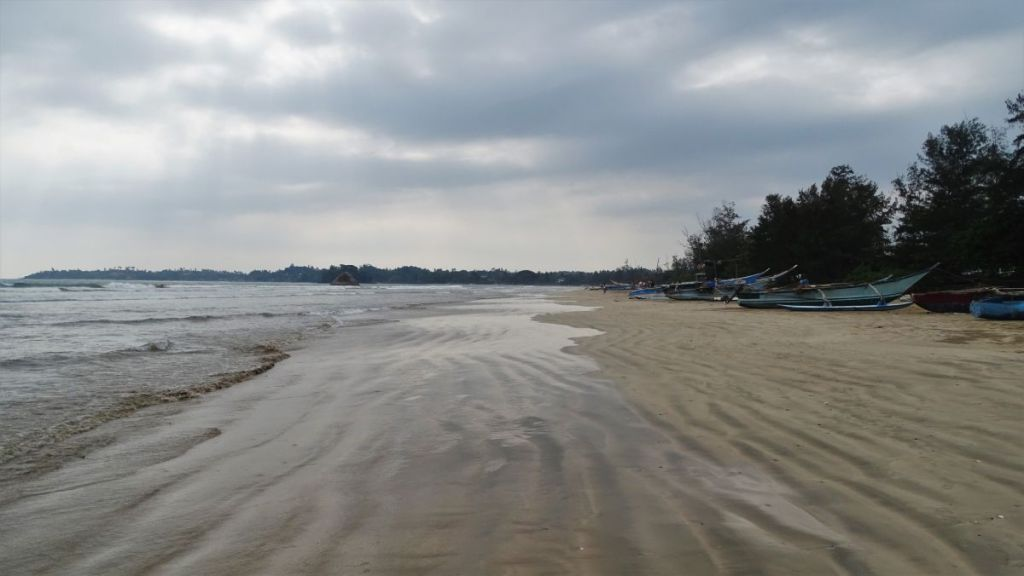 Cloudy sky over a long, empty sandy beach and a row of traditional wooden fishing boats in Weligama, Sri Lanka
